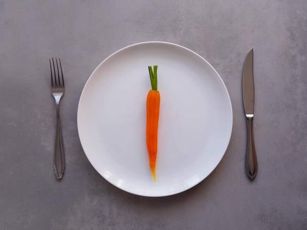 plato con una zanahoria y unos cubiertos
